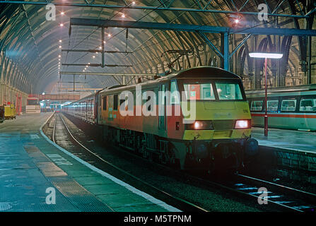 A class 90 electric locomotive number 90018 waits to depart London Kings Cross station with a travelling post office - Stock Photo