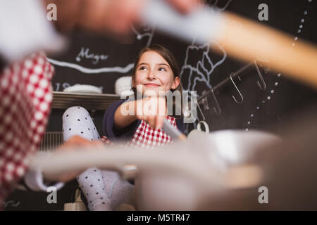 A small girl cooking with grandmother at home. - Stock Photo