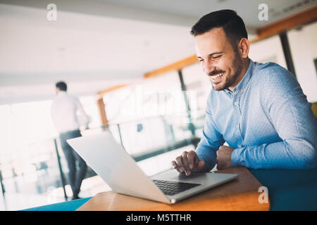 Young handsome architect working on laptop in office - Stock Photo