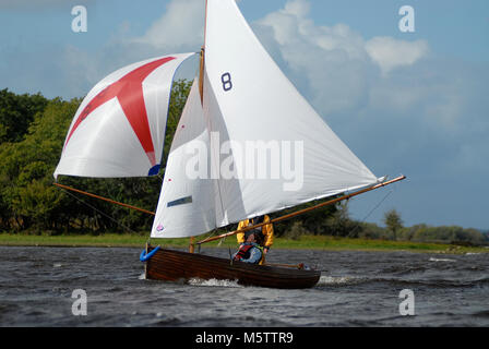 A traditional Water Wag dinghy races down Lough Ree during the Irish sailing raid on the Shannon River in Ireland. - Stock Photo