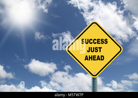 Success just ahead yellow road sigh against blue cloudy sky - Stock Photo