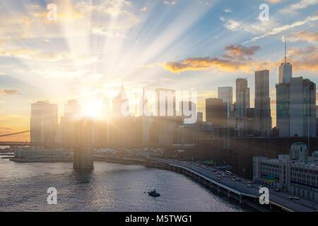 Sunlight shines behind New York City skyline - Stock Photo