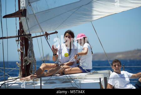 The Sakelariou family enjoy a day out on the fibreglass cutter Kivoto (the Ark) sailing off Syros, Greece. - Stock Photo