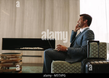 Side view of smiling businessman with laptop talking on cellphone at the airport waiting lounge. Business traveler - Stock Photo