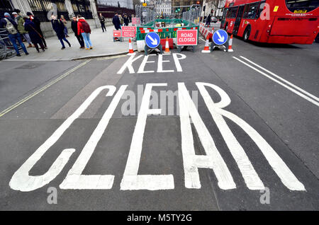London, England, UK. 'KEEP CLEAR' painted on the road in front of the Houses of Parliament during roadworks - Stock Photo