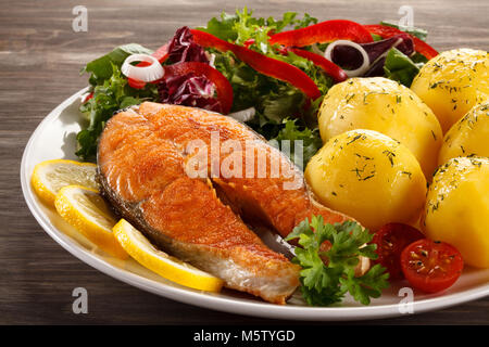 Fried salmon and vegetables on wooden table - Stock Photo