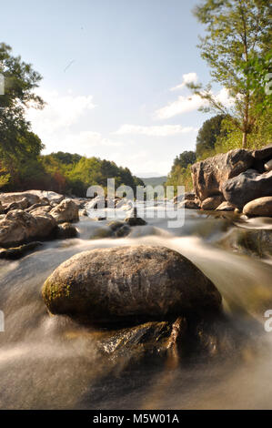 Fast flowing water down a river. Taken on the island of Corsica - Stock Photo