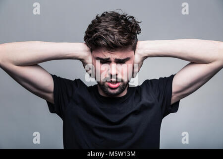I need silence. Frustrated young man in shirt and tie covering ears with hands and keeping eyes closed while standing - Stock Photo