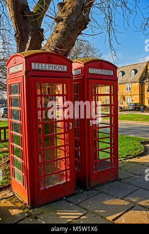 Two iconic red telephone kiosks on the High Street in the Cotswolds town of Broadway. - Stock Photo