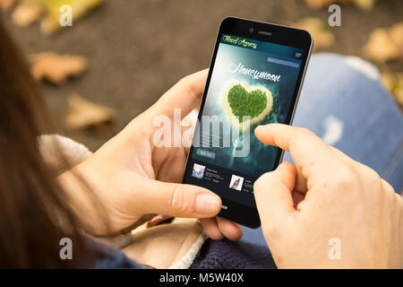 mobile design concept: woman holding a 3d generated smartphone with travel honeymoon on the screen. Graphics on - Stock Photo