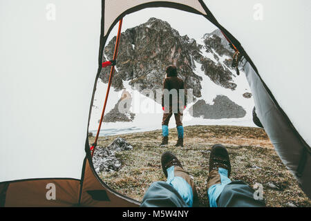 Camping traveling couple view from tent entrance woman walking in mountains man feet relaxing inside Lifestyle concept - Stock Photo