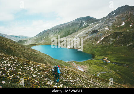 Man with backpack hiking to lake in mountains Lifestyle traveling survival concept adventure outdoor active vacations - Stock Photo