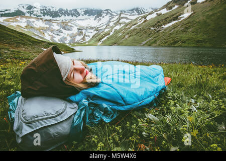 Woman relaxing in sleeping bag laying on grass enjoying lake and mountains landscape Travel Lifestyle camping concept - Stock Photo