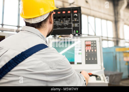 Back view of bearded operator wearing protective helmet focused on work while sitting in front of CNC machine, interior - Stock Photo