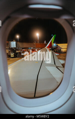Airplane departing at evening time. Airdrome and another aircrafts are seen from aircraft window - Stock Photo