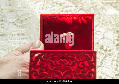 Female hand holding a red box with a ring on the background of the lace napkin, selective focus - Stock Photo