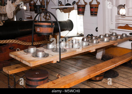 A sailors laid mess table ( historical recreation ) between cannon / guns on the Gun Deck of HMS Warrior. Portsmouth - Stock Photo