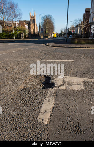 Large pot hole in the middle of a main road - Stock Photo