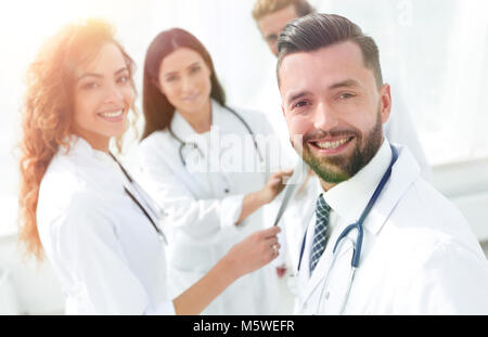 Portrait of aged male doctor teaching medical students. - Stock Photo