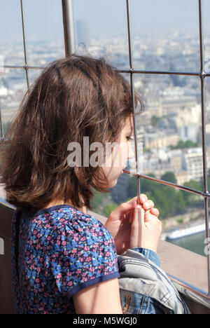 The girl looks through the grille of the Eiffel tower at the sprawling below the city of Paris. - Stock Photo