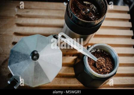 Preparing fresh coffee in moka pot on electric stove. Measuring ground coffee for moka pot. - Stock Photo