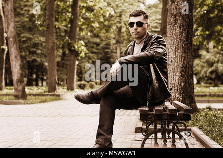 Tinting a photo in brown tones with a young man in a park in sunglasses and a leather jacket - Stock Photo