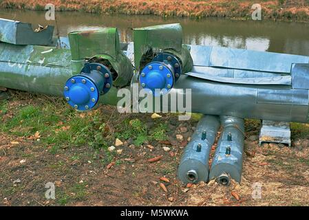 Hot steam heating system pipelines. Ball valves with blind flanges.  City buldings in the background.
