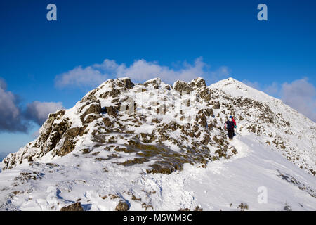 Hikers hiking down south ridge at Bwlch Main from summit of Mt Snowdon peak with snow in winter in Snowdonia National - Stock Photo