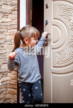 A little girl came into the apartment and closes the door. - Stock Photo