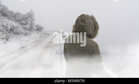 Wintry scene with snow and woman near road. Back of the female figure in winter windbreaker with a hood standing - Stock Photo