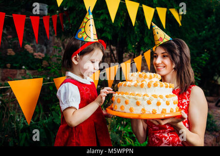 Children's party and cake. A small child of a funny girl is trying to finger a large two-story cake that mom near - Stock Photo