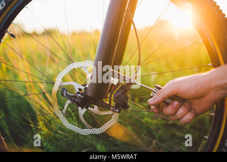 man screws the front wheel with hydraulic disc brake on the mtb bicycle. - Stock Photo