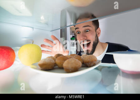 Excited Young Man Looking At Cookie In Refrigerator - Stock Photo