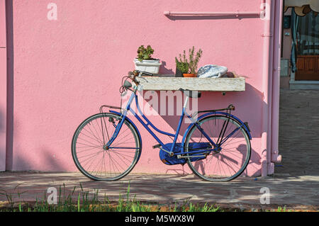 Close-up of bicycle leaning against colorful wall on a sunny day in Burano, a gracious little town full of canals, - Stock Photo