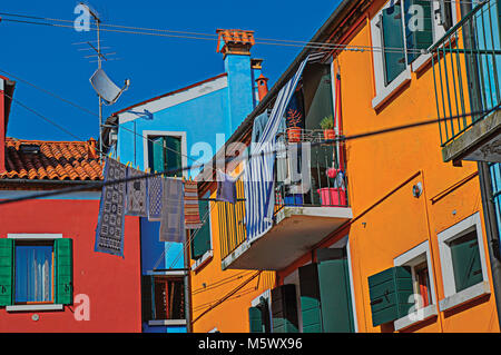 View of colorful terraced houses, balcony and clothes hanging in an alley at Burano, a cute little town full of - Stock Photo