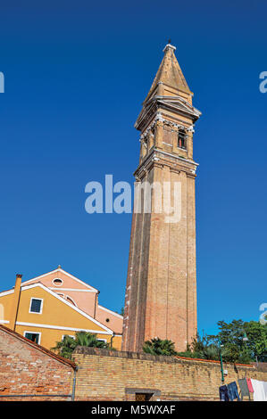 Overview of colorful buildings and leaning bell tower in a blue sunny day at Burano, a gracious little town full - Stock Photo
