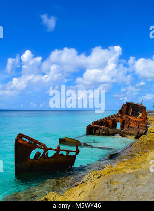 A shipwreck lies rusting in the crystal clear waters of the beautiful Caribbean island of North Bimini, Bahamas - Stock Photo