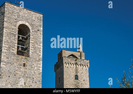 View of the stone towers with bells on the sunny blue sky at San Gimignano. A medieval town famous for having several - Stock Photo