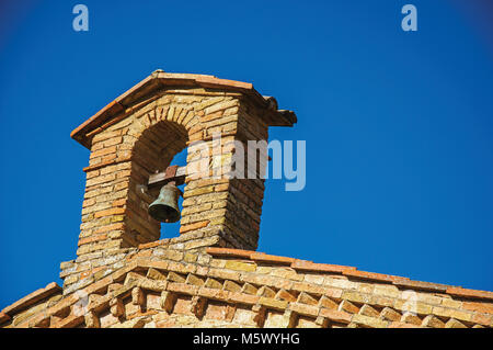 View of bell on top of brick church and blue sunny sky at San Gimignano. A medieval town famous for having several - Stock Photo