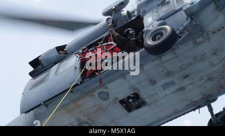 """A Naval Air Crewman assigned to the """"Island Knights"""" of Helicopter Sea Combat Squadron (HSC) 25 lowers a litter - Stock Photo"""