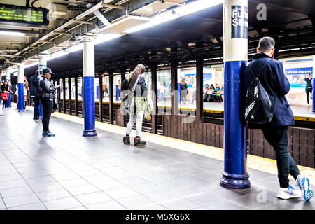New York City, USA - October 28, 2017: People waiting in underground transit empty large platform in NYC Subway - Stock Photo