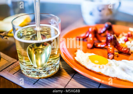 Closeup of large breakfast brunch plate with fried eggs, hash browns shredded potatoes, sausage tako octopus, collagen - Stock Photo