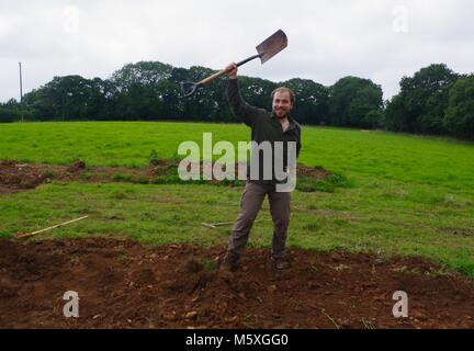 Young Handsome Man Manually Digging a Grassy Field in Mid Devon to Build a Poly Tunnel. Lydcott Nursery, Morchard - Stock Photo