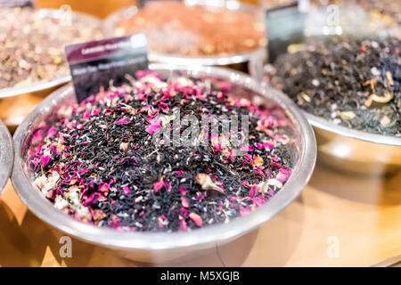 Closeup of black rose tea spices on display in metal bowl tray filled with rosebuds petals mix, sign - Stock Photo