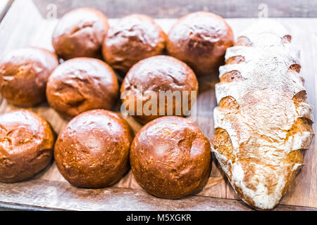 Closeup of fresh brown scored sourdough baked bread loaves in bakery with many buns rolls - Stock Photo