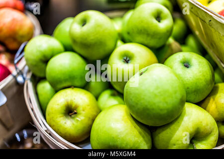 Closeup of many granny smith green yellow apples in wooden basket at farmer's market shop store showing detail and - Stock Photo