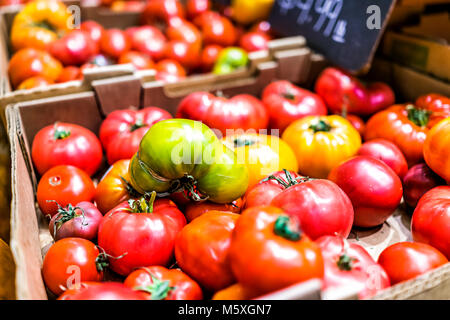 Closeup of many juicy vibrant, ripe large red, yellow, green heirloom tomatoes on display farmers market shop store - Stock Photo