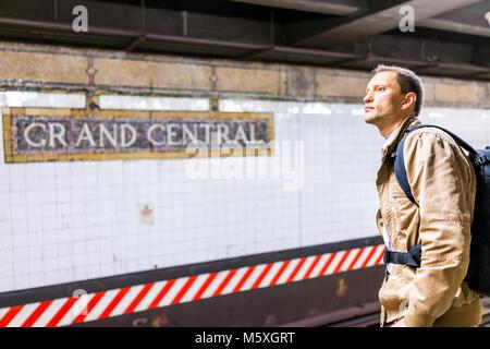 New York City, USA - October 29, 2017: Closeup of young man waiting in underground transit empty large platform - Stock Photo