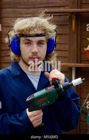Young Man with a Power Tool Undertaking DIY Home Improvement Work in a British Working Class Garden. Exeter, Devon, - Stock Photo