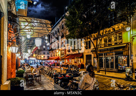 A woman tourist walks along a lively street in the Latin Quarter of Paris France with colorful cafes, shops and - Stock Photo